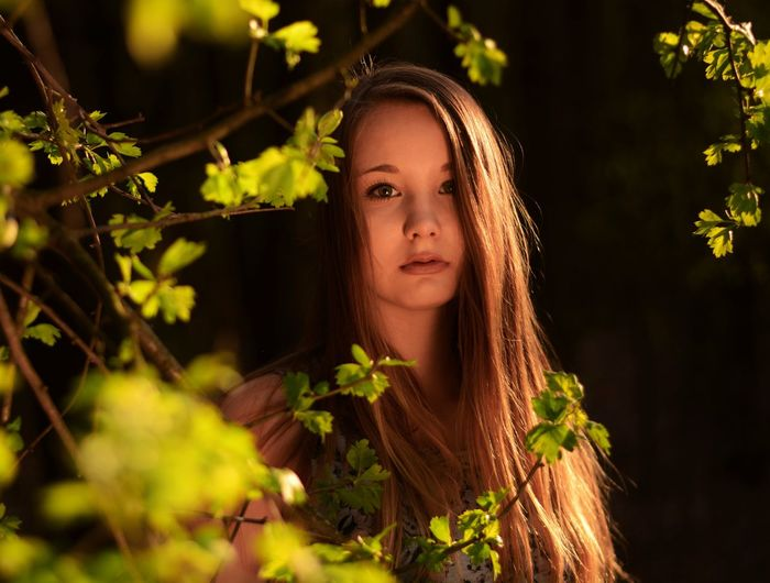 Close-up portrait of teenage girl by plant