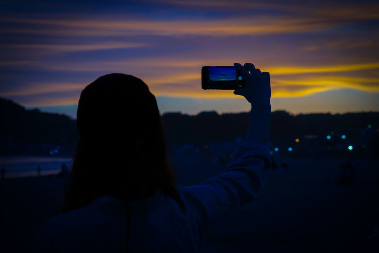 Rear view of person photographing against sky during sunset