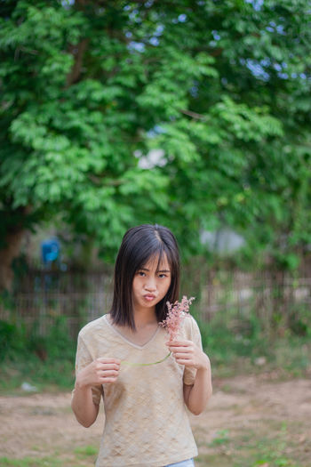 Portrait of beautiful young woman holding flower standing against tree