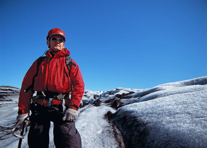 Man standing on snow covered landscape against clear blue sky