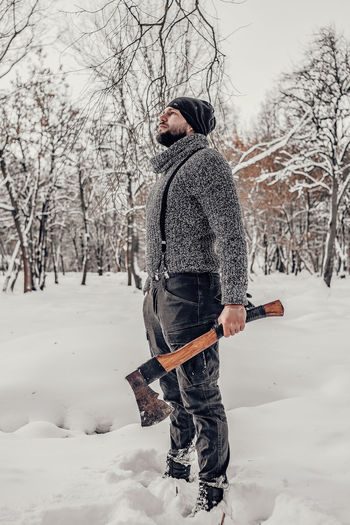 Side view of man on snow covered field