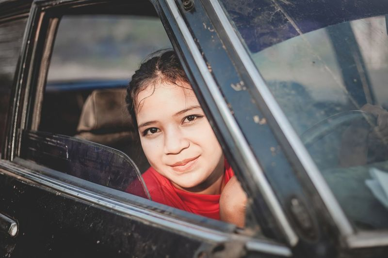 Close- up portrait of young beautiful women sitting a car.