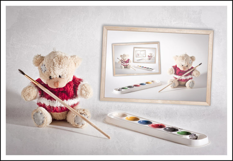 Pallet by teddy bear by picture frame against white background