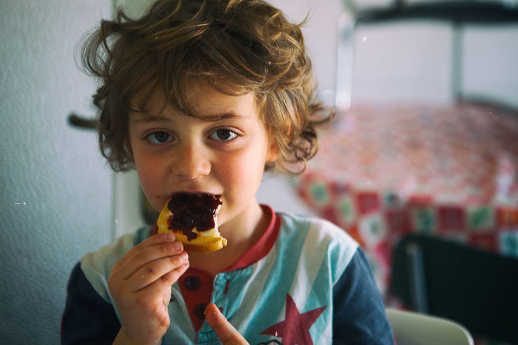 Portrait of boy eating rusk with strawberry jam at home