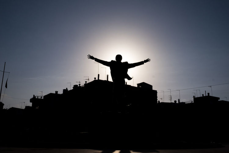 Silhouette of man with arms outstretched against buildings