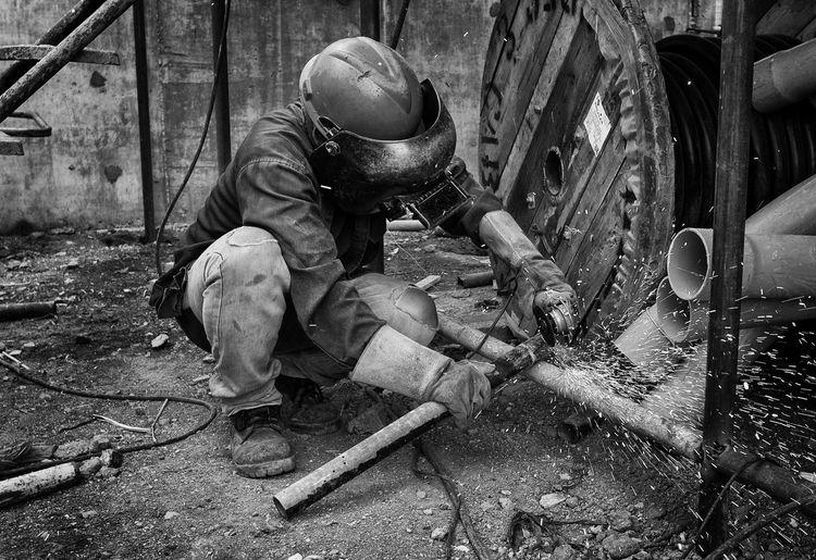 Manual worker welding metal at workshop