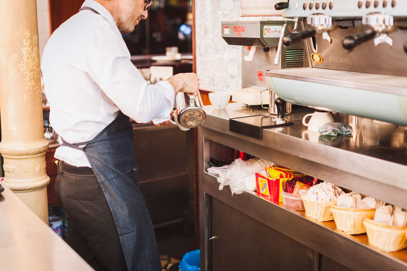 Midsection of male owner pouring coffee in cup