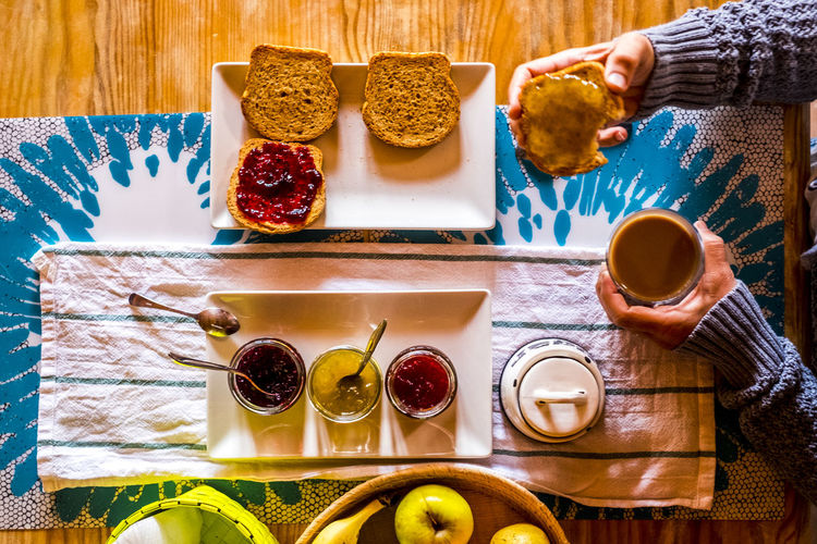 Cropped hands of woman having breakfast at table