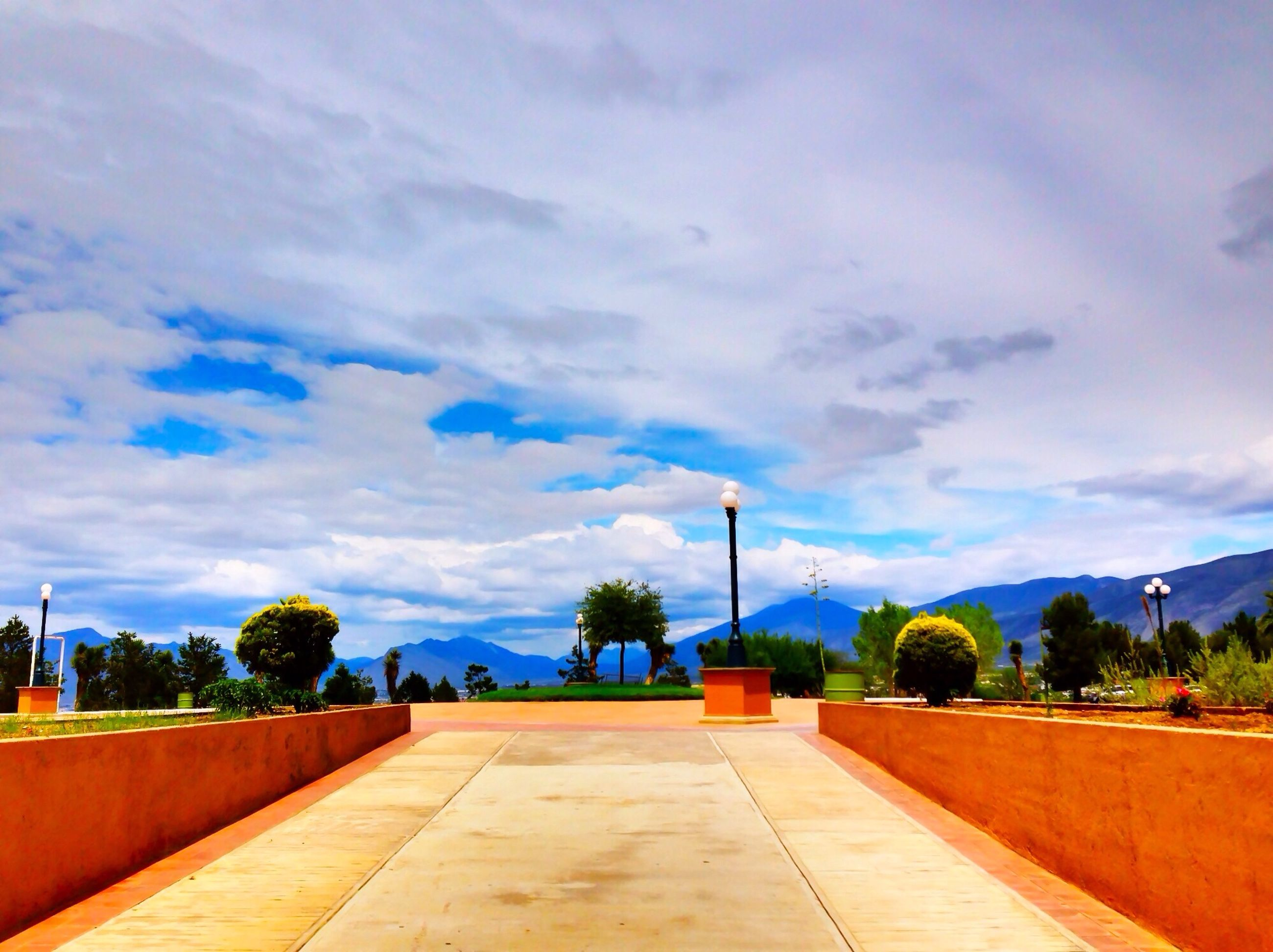 sky, tree, cloud - sky, the way forward, cloud, tranquility, tranquil scene, blue, nature, scenics, cloudy, beauty in nature, built structure, footpath, empty, road, palm tree, railing, outdoors, architecture