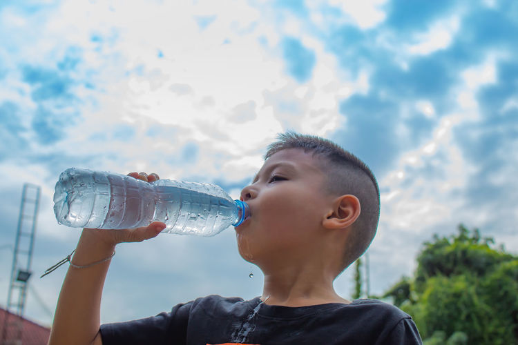 The boys are drinking cold water. Bottle Child Childhood Cloud - Sky Container Drink Drinking Drinking Water Food And Drink Glass Headshot Holding Leisure Activity Lifestyles Males  Men Nature One Person Outdoors Real People Refreshment