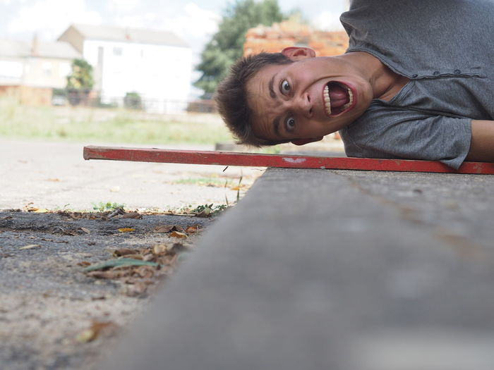 Portrait of young man screaming while lying on floor