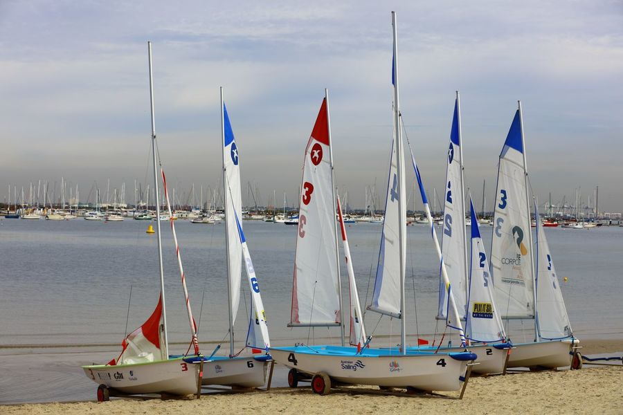 A group of small sail boats trailered up on the beach, which I was to learn later on, were going to be used in a racing regatta in the inner harbour soon afterwards. Beach Calm Water EyeEmNewHere Inner Harbour Multi Colours Overcast Sky Sailing Boats Sails Sand Seawater