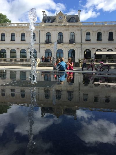 Water Cloud - Sky Reflection Architecture Real People Sky Building Exterior Built Structure Waterfront Day Outdoors Men Leisure Activity Lifestyles Vacations Puddle Nature Women Adults Only Adult