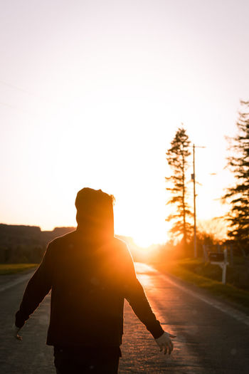 Rear View Of Silhouette Man Standing On Road Against Sky During Sunset