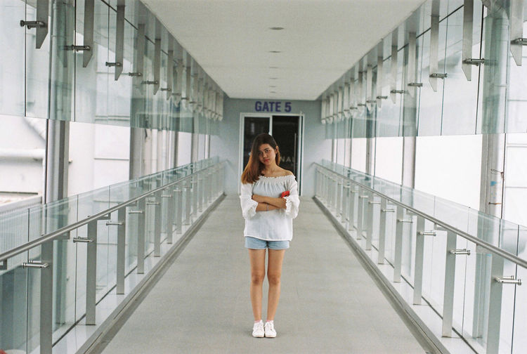 Portrait of young woman with arms crossed standing in corridor