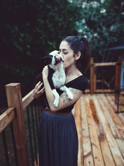 Woman kissing dog while standing outdoors