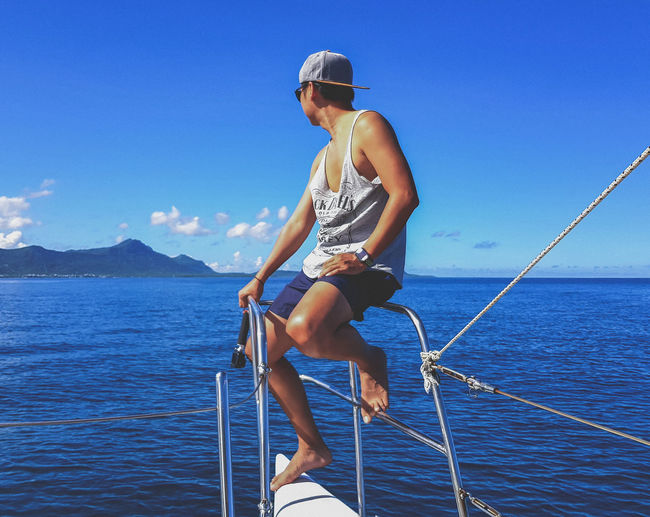Man on sailboat against sea against sky