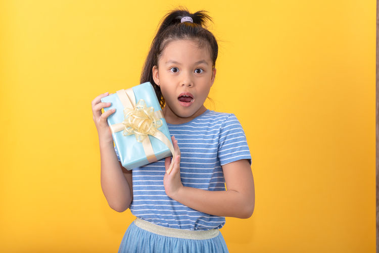 Portrait of girl standing against yellow background