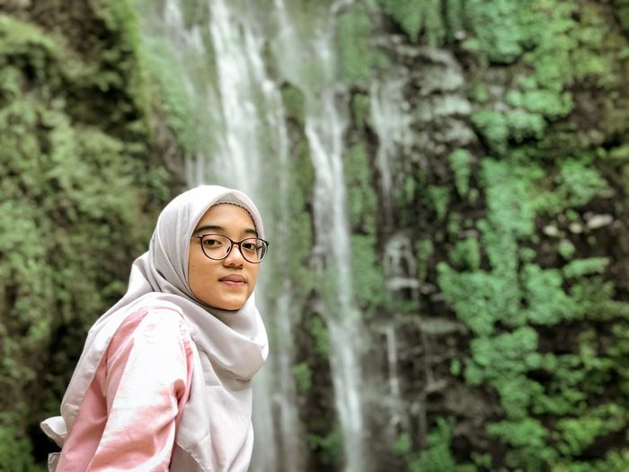 Portrait of young woman against waterfall and trees in forest