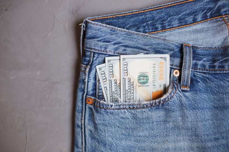 Directly above shot of paper currencies in jeans pocket on gray background