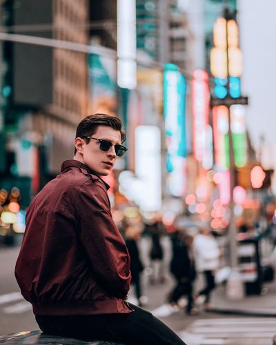 Young man wearing sunglasses standing on street in city