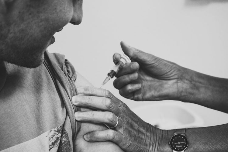 Injection Adult Close-up Day Holding Human Hand Immunization Indoors  Injecting Men People Real People Smiling Syringe Two People Vaccine Working