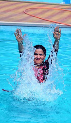 Woman splashing water while swimming in pool