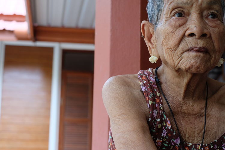Senior Woman Looking Away Against House