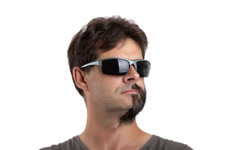 Portrait of young man wearing sunglasses against white background