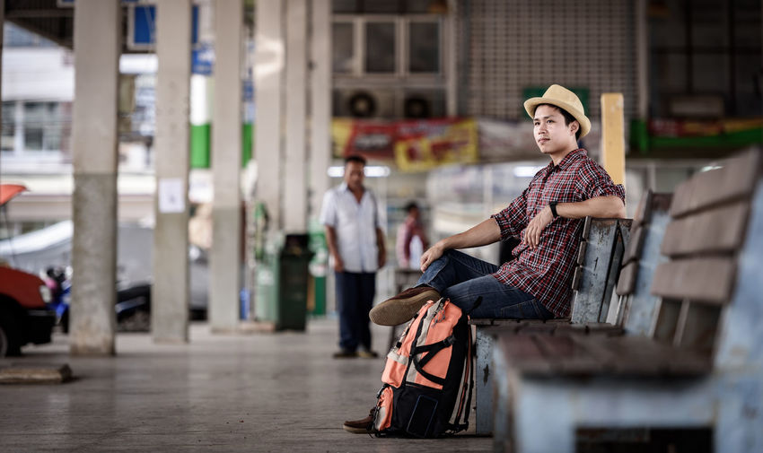 Side view of male tourist sitting on bench in city