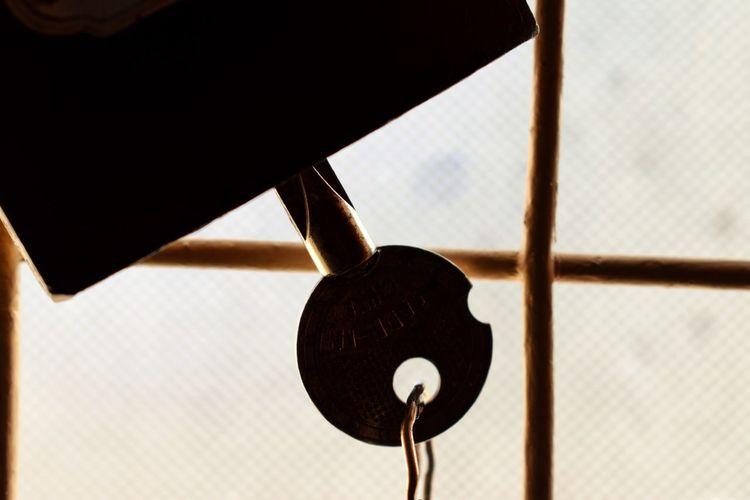 Close-up of key hanging in padlock