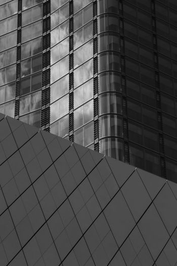 Low angle view of glass building in city against sky