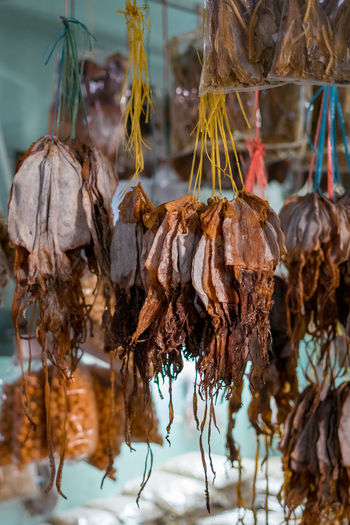 Dried fish tied into several bundles for sale, hanging from above, in a local market in sabah.