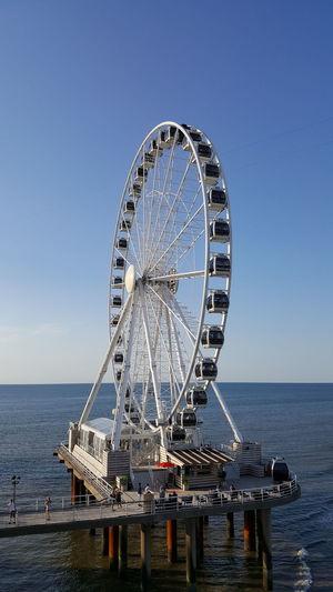 Ferris wheel by sea against clear blue sky