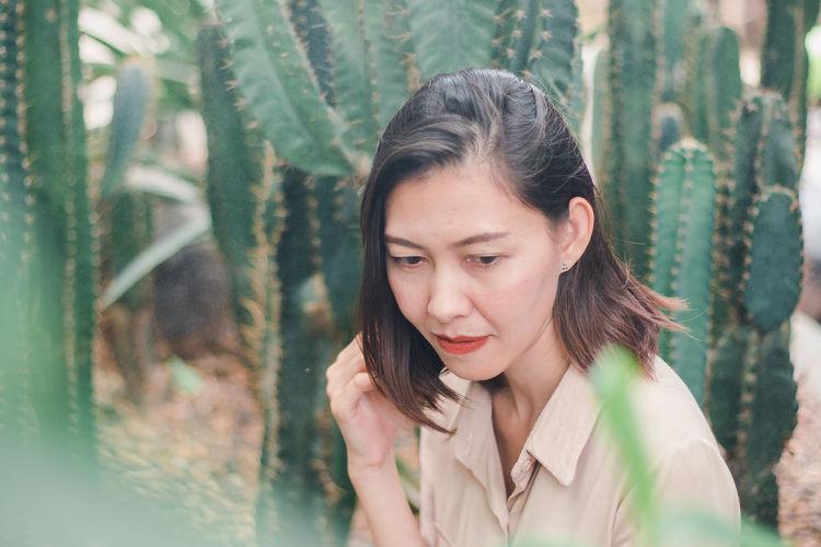 Woman looking away against cactus