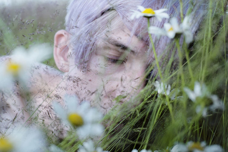 Close-Up Of Teenage Boy Sleeping By Flowers