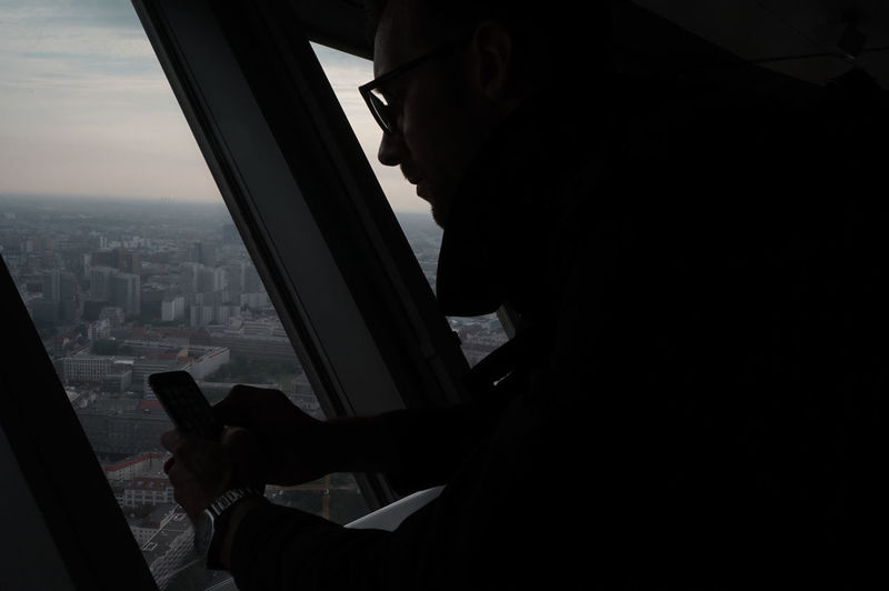 Side view of man using mobile phone in city