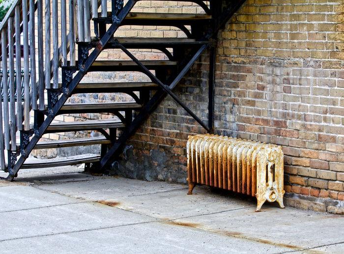 Metallic structure on sidewalk against brick wall