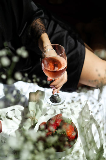 Close-up of hand holding a glass of rose wine