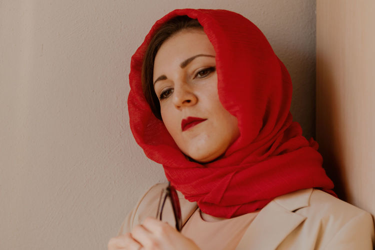Portrait of beautiful young woman against red wall