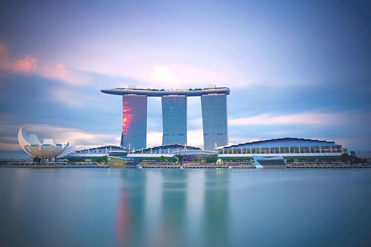 Marina bay sands and artscience against cloudy sky during sunset