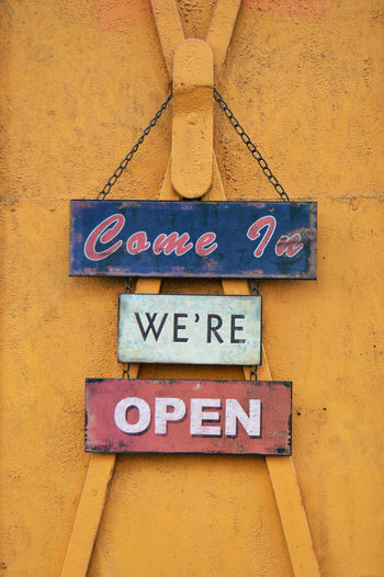 Come in we're open sign hanging on coffee shop door Coffee Shop Door Sign Hanging Modern Sign Typography Typography & Design Board Sign Close-up Coffee Shop Door Come In Sign Communication Design Hipster Metal Art Open Open Sign Outdoors Retro Styled Rustic Style Signboard Text Title Urban Yellow
