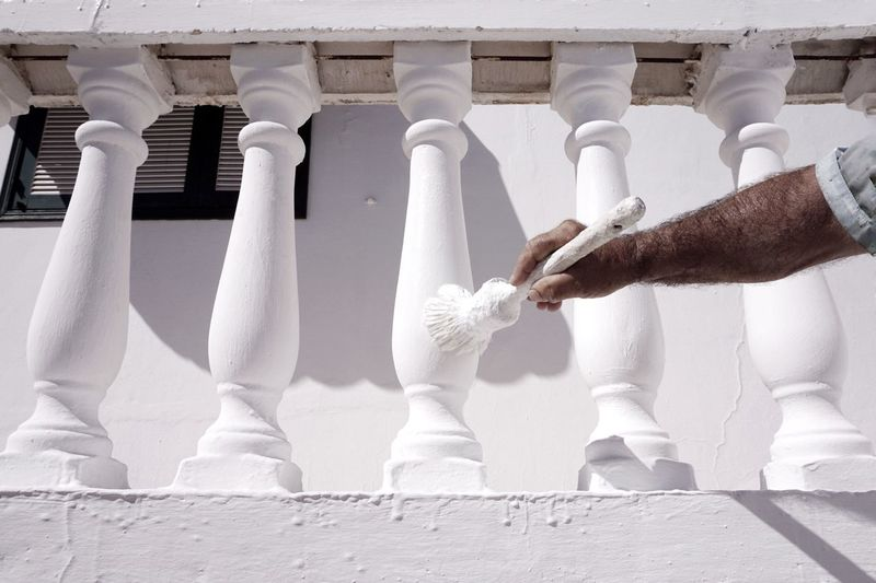Cropped Image Of Worker Painting Balustrade