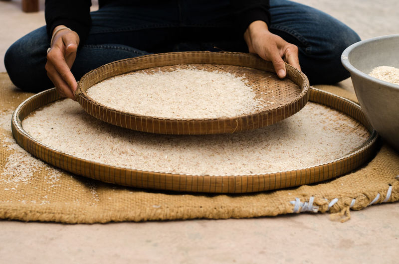 Low Section Of Person Sieving Rice In Wicker Plate