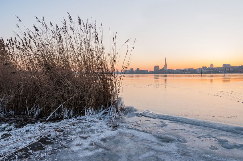 View over the river Warnow to Rostock, Germany. Frozen Holiday Ice Morning Rostock Winter Architecture Building Exterior City Day Nature No People Outdoors Reeds River Sky Snow Sunrise Sunup Tourism Town Travel Destinations Vacation Warnow Water