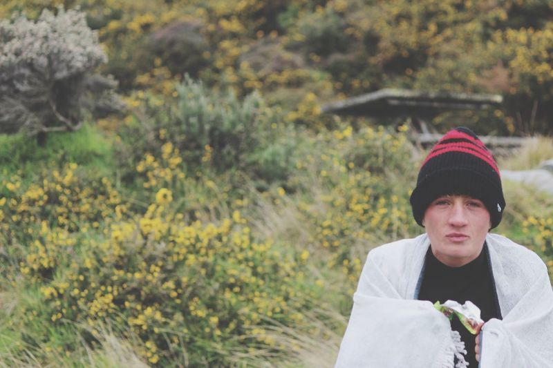 Portrait of young man shivering against plants at park