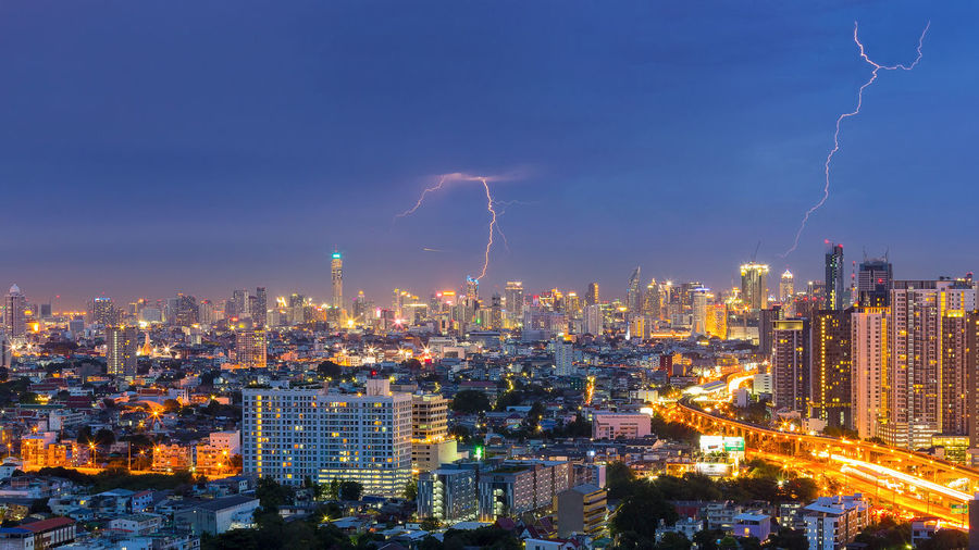 High Angle View Of Illuminated City Against Lightning At Dusk
