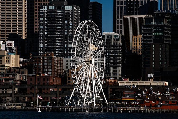 View of ferris wheel against buildings in city