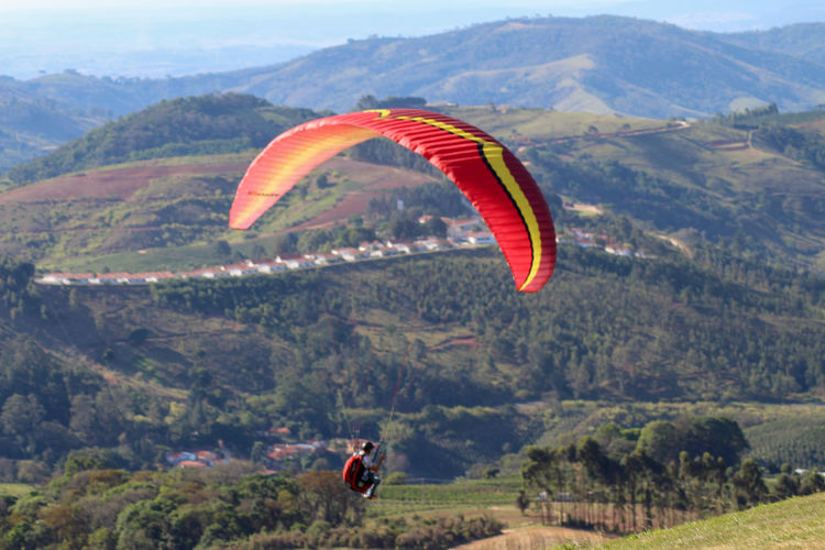 Person paragliding over mountains