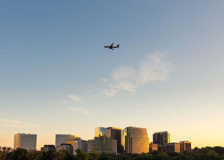 Low Angle View Of Airplane Flying Over Buildings